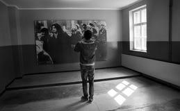 奥斯威辛,波兰- 2012年3月30日:有拍一张海报的照片在其中一个的耳机的游人营房里面 免版税图库摄影