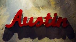 奥斯汀得克萨斯垂悬在织地不很细墙壁上的金属标志 图库摄影