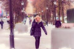 奥斯陆,挪威- 2018年3月, 26日:使用她的手机的室外观点的美丽的白肤金发的妇女和走在一个公园 免版税库存图片
