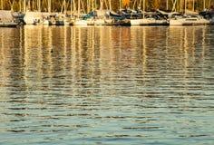 奥斯陆-海湾、小船和蓝色挥动在金黄日落 库存图片