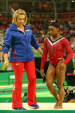 奥林匹克冠军西蒙妮胆汁R和教练在最后的竞争前的Aimee Boorman在平衡木妇女` s艺术性的体操 免版税库存照片