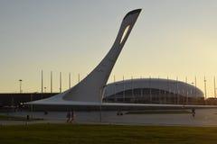 奥林匹克火炬以冰宫殿` bolshoj `为背景和在清楚的天空的背景中在天的日落的 库存照片