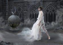 奥秘。 在老发烟性城堡的魔术妇女剪影。 神秘古老风景 库存照片