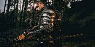 奥秘装甲的疤痕面部骑士有剑的和石弓在森林里 免版税库存图片