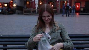 女人坐在木凳上,从背包里拿出香蕉,背在一座彩绘房屋的背景下 股票录像