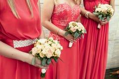 女傧相同样穿戴了与玫瑰和其他flo花束  免版税图库摄影