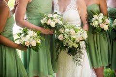 女傧相和新娘有美丽的绿色,桃红色和白色玫瑰的 图库摄影