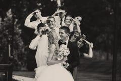女傧相和男傧相看一个亲吻的婚礼夫妇立场 图库摄影