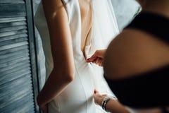 女傧相在早晨帮助用拉锁拉上她的礼服的一个新娘,新娘为婚礼那天做准备 免版税图库摄影