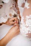 女傧相帮助新娘投入婚礼礼服 免版税库存图片