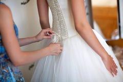 女傧相帮助新娘 免版税库存图片
