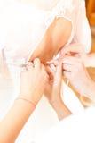 女傧相帮助的新娘 免版税库存图片
