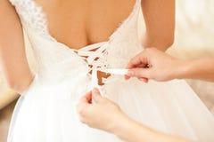 女傧相帮助的新娘 库存图片