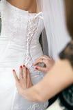 女傧相帮助给新娘投入婚礼礼服 免版税库存照片