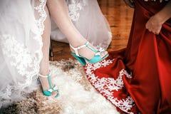 女傧相帮助给新娘投入婚礼鞋子 免版税图库摄影