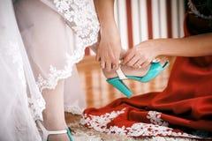女傧相帮助给新娘投入婚姻的鞋子 免版税库存图片