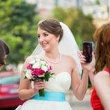 女傧相拍一个年轻愉快的新娘的照片 免版税图库摄影