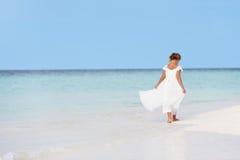 女傧相礼服的女孩走在美丽的海滩的 免版税库存照片