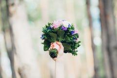 女傧相被捉住的婚姻的花束 女性手拿着花束在上面 免版税图库摄影