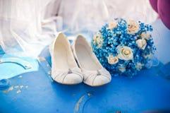 女傧相鞋子和蓝色花束 库存图片