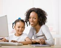 女儿专用执行帮助的家庭作业母亲 免版税库存照片