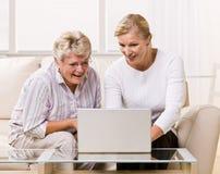 女儿使用妇女的膝上型计算机前辈 库存照片