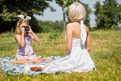 女儿使用摄影师和母亲的模型户外 库存照片