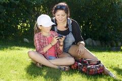 女儿和姐妹使用与电话 图库摄影