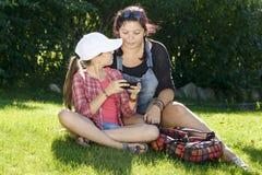 女儿和姐妹使用与电话 免版税图库摄影