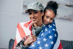 女儿和战士包裹与美国国旗 库存照片