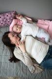 女儿和母亲一起是愉快的,有ba的滑稽的嬉戏的妈咪 图库摄影
