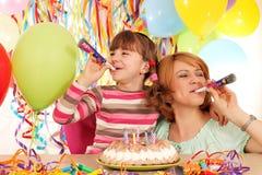 女儿和母亲有喇叭和气球的在生日 免版税库存图片