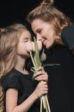 女儿和母亲有郁金香的开花微笑在黑色 免版税库存照片