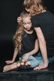 女儿和母亲有郁金香的开花拥抱在黑色 免版税图库摄影