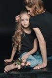 女儿和母亲有郁金香的开花拥抱在黑色 免版税库存照片