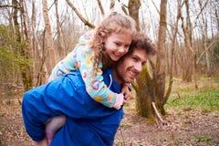 给女儿在乡下步行的父亲肩扛乘驾 库存照片