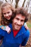 给女儿在乡下步行的父亲肩扛乘驾 免版税库存照片