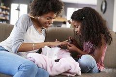 女儿在家坐绘母亲` s钉子的沙发 库存图片