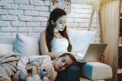 女儿在母亲的膝盖睡觉 免版税库存图片