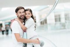 女儿坐父亲的膝部在购物中心 爸爸和女孩微笑着 免版税库存图片