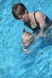 女儿她教的小的母亲游泳 免版税库存照片