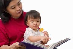 女儿她母亲讲故事 免版税库存照片