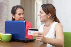 女儿帮助在线购物成熟的母亲 免版税库存图片