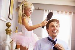 女儿帮助父亲准备好工作掠过头发 免版税库存照片