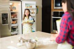 女儿帮助的妈妈在厨房里 免版税库存图片