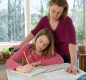 女儿帮助的家庭作业妈妈 免版税图库摄影