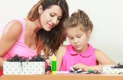 女儿帮助的家庭作业妈妈 免版税库存图片