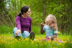 女儿开花室外的母亲 免版税库存图片