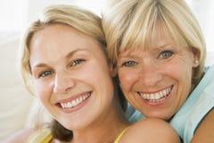 女儿微笑增长的母亲  免版税库存图片