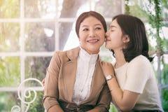 女儿拥抱和亲吻她的母亲 图库摄影
